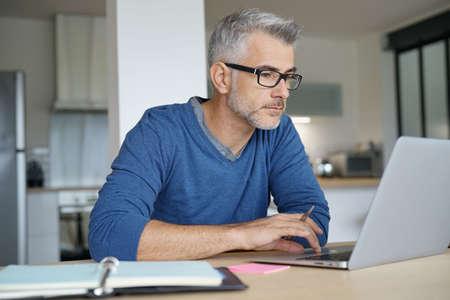 Foto de Middle-aged man working from home-office on laptop - Imagen libre de derechos