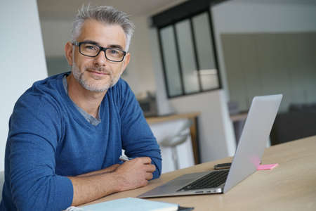 Photo for Middle-aged man working from home-office on laptop - Royalty Free Image