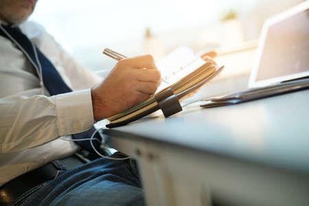 Closeup of businessman writing on agenda