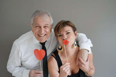 Photo pour Cheerful senior couple with photobooth props, isolated - image libre de droit