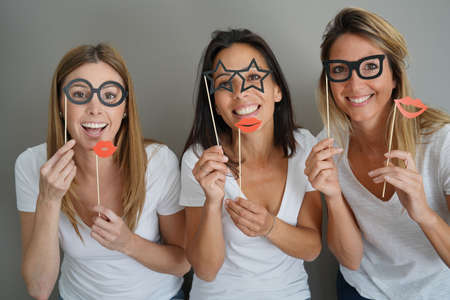 Photo pour Girls having fun playing with photobooth props - image libre de droit