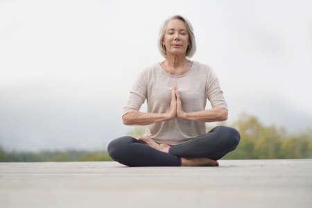 Foto de Serene senior woman meditating outdoors - Imagen libre de derechos