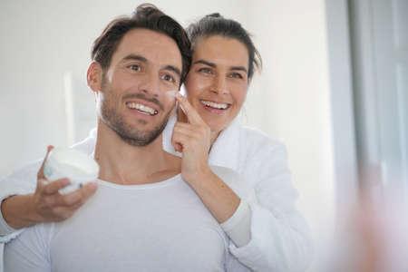 Photo pour Stunning brunette applying face cream on her handsome partner - image libre de droit