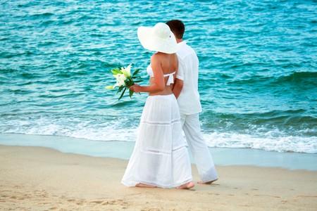 Foto de Romantic young couple walking along the sea - Imagen libre de derechos