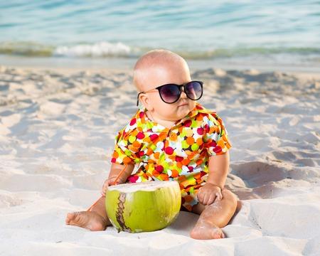 Foto de Funny baby wearing sunglasses with coconut - Imagen libre de derechos