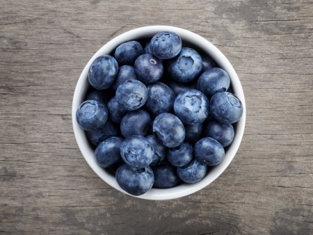 Photo for fresh blueberries in white bowl on wood table, rustic style - Royalty Free Image