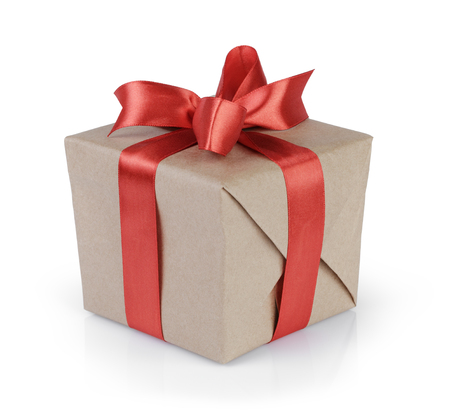 Foto de cube gift box wrapped with kraft paper and red bow, isolated - Imagen libre de derechos