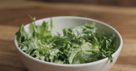 frillis salad leaves falling into white bowl