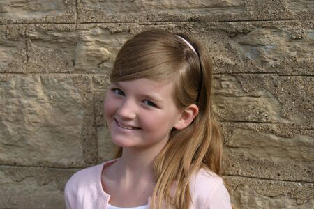 pretty blonde preteen girl in pink smiling outdoors by stone wall