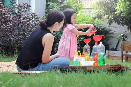 Foto de Asian mom and little daughter experiment with different water colors mixing for learning and strengthen Imagine. - Imagen libre de derechos