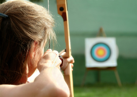 Photo for Archer spans the bow and aims to target  - Royalty Free Image