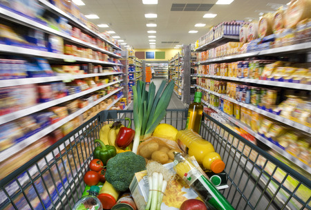 Photo pour Shopping cart with foods at the grocery store - image libre de droit