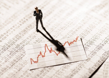 Photo pour Model figure stands on rate tables and looks skeptically on a graph with stock prices. - image libre de droit