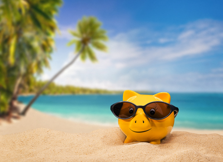 Photo for Yellow piggy bank with sunglasses with a tropical beach in the background - Royalty Free Image