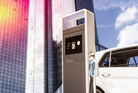 Foto per E-car at a charging station in front of a skyscraper - Immagine Royalty Free