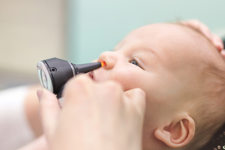 Photo for Infant in pediatric clinic. Close-up doctor's hand with modern otoscope examining baby's nose. Children healthcare and disease prevention. - Royalty Free Image