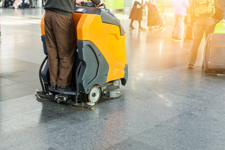 Foto de Man driving professional floor cleaning machine at airport or railway station.  Floor care and cleaning service agency.  - Imagen libre de derechos