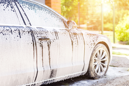 Foto de Manual car wash. Washing luxury vehicle with white foamy detergent. Automobile  cleaning self service - Imagen libre de derechos