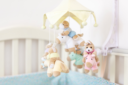 Foto de Close-up baby crib with musical animal mobile at nursery room. Hanged developing toy with plush fluffy animals. Happy parenting and childhood, expectation delivery of a child concept - Imagen libre de derechos