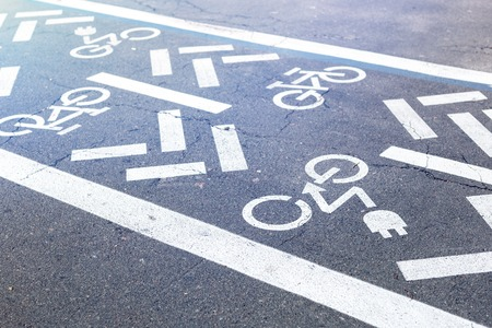 Foto de Asphalt road with bicycle and electric transport lane. Cycle and zero emission vehicles white sign on floor. Recreation area for green energy transport in city park. - Imagen libre de derechos