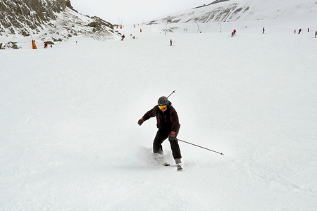 Foto de Mature skier fallen during downhill at ski resort in winter. Accident at ski slope due to unfasten ski binding. Extreme winter sport activities. - Imagen libre de derechos
