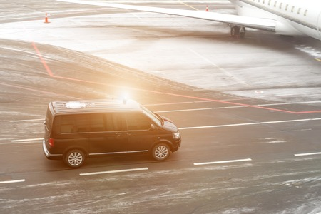 Photo pour Black VIP service van running on airport taxiway with blurred private jet on background. Business class service at airport. Security intelligence agency hurrying at airfield - image libre de droit
