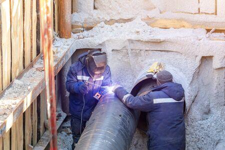 Foto de Welder welding water or gas steel pipeline with assistant worker in trench. City underground utilitites renewal and replacement, - Imagen libre de derechos