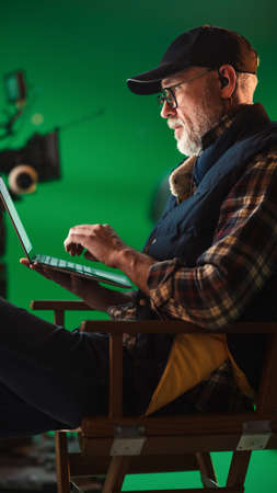 Photo for Prominent Successful Director Sitting in a Chair on a Break and Using Laptop Computer. On the Studio Film Set with High-End Equipment Professional Crew Shooting High Budget Movie - Royalty Free Image