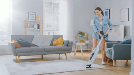 Foto de Young Beautiful Woman in Jeans Shirt and Shorts is Vacuum Cleaning a Carpet in a Bright Cozy Room at Home. She Uses a Modern Cordless Vacuum. Shes Happy and Cheerful. - Imagen libre de derechos