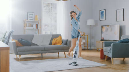 Foto de Young Beautiful Woman in Jeans Shirt and Shorts is Listening to Music on Her Headpones, Dancing and Vacuum Cleaning a Carpet in a Cozy Room at Home. She Uses a Cordless Vacuum. Shes Happy and Joyful. - Imagen libre de derechos