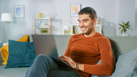 Foto de Handsome Man Uses Laptop Computer while Sitting on Sofa at Home. Man Working, Browsing Through Internet from His Cozy Living Room. - Imagen libre de derechos
