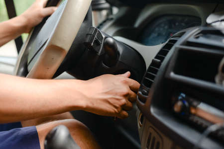 Photo pour Driver turning on the ignition on the dashboard of a car - image libre de droit