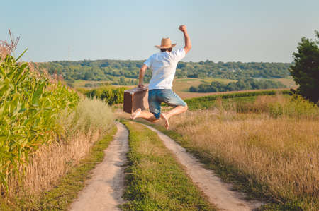Photo pour Picture of man in straw hat holding old valize and jumping on country road. Backview of excited traveller on blurred sunny outdoor background. - image libre de droit