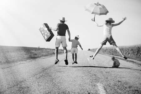 Black and white picture of joyful happy family jump on country road in summer. Back view of parents and two kids with suitcase and umbrella on sunny countryside background.