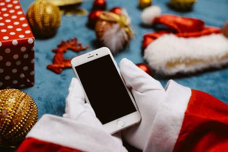 Foto de Oslo, Norway - above closeup on Santa Claus holding phone, festive top view shot. Smart communication wireless technology commerce. Shopping ideas browsing organizer - Imagen libre de derechos