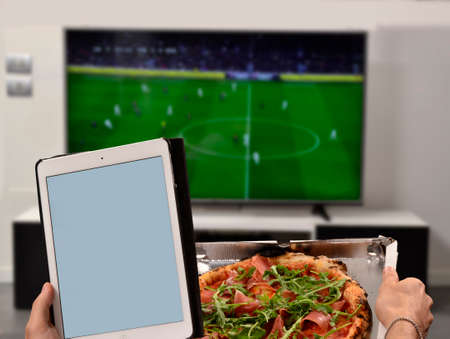 Foto für Watching television eating pizza and holding computer tablet. - Lizenzfreies Bild