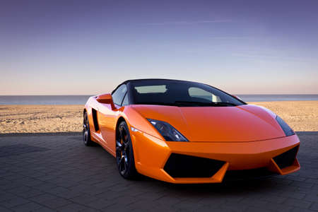 Sleek looking fast sports car background near sand