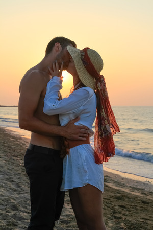 Happy young couple in their twenties, tenderly embracing and kissing at the beach just before sunset.