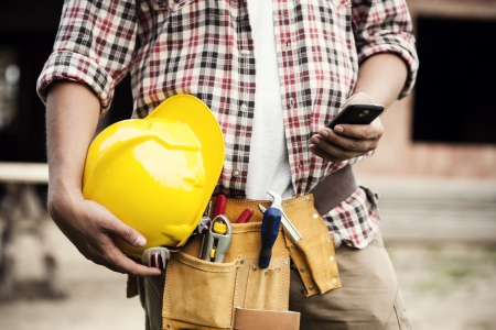 Photo pour Close-up of construction worker texting on mobile phone - image libre de droit