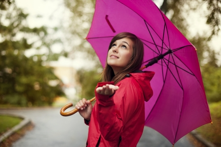 Beautiful woman with umbrella checking for rain