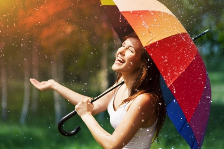 Photo pour Laughing woman with umbrella checking for rain - image libre de droit