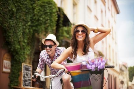 Foto de Happy couple chasing each other on bike - Imagen libre de derechos