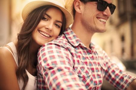 Photo pour Close up of loving couple riding on bike in the city - image libre de droit
