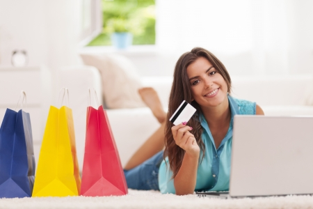 Photo pour Beautiful woman paying by credit card for shopping at home  - image libre de droit