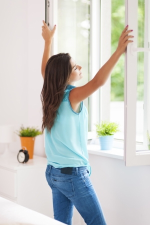 Photo pour Young woman opening window in living room  - image libre de droit