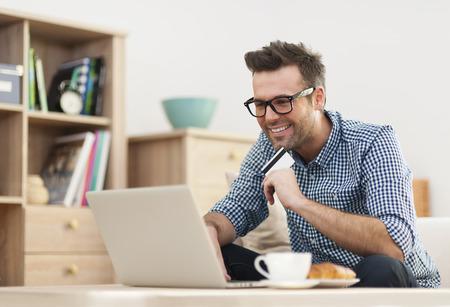 Foto de Happy man sitting on sofa with laptop and credit card  - Imagen libre de derechos