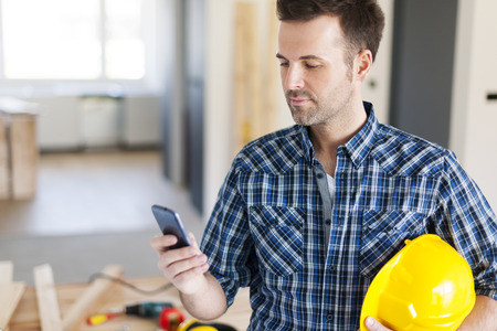 Photo for Construction worker with contemporary mobile phone  - Royalty Free Image