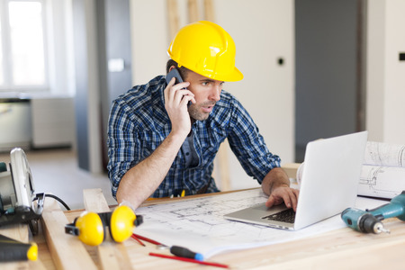 Photo for Man talking on mobile phone and using laptop on construction side  - Royalty Free Image