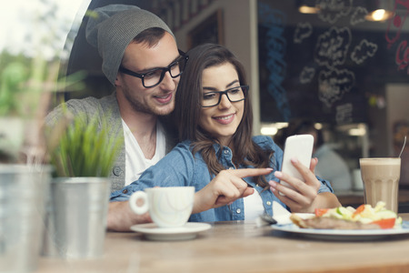 Photo for Embracing couple using mobile phone in cafe  - Royalty Free Image