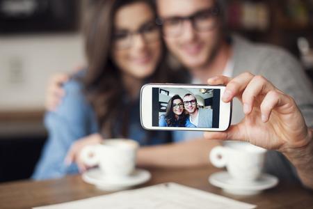 Photo pour Loving couple taking selfie at cafe - image libre de droit